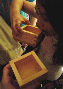 A Japanese girl drinking sake from a masu.