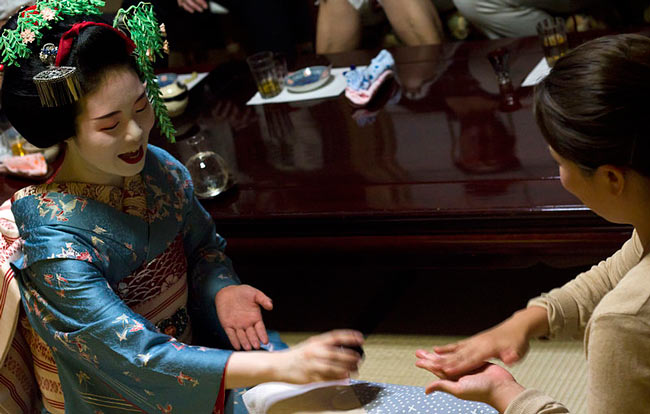 A geisha entertaining a client with a game of konpira fune fune.