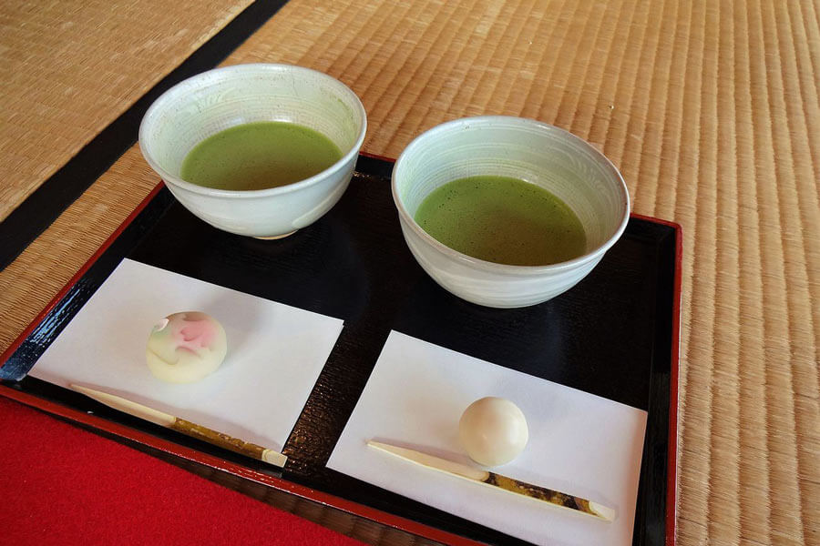 Two cups of matcha served with wagashi.
