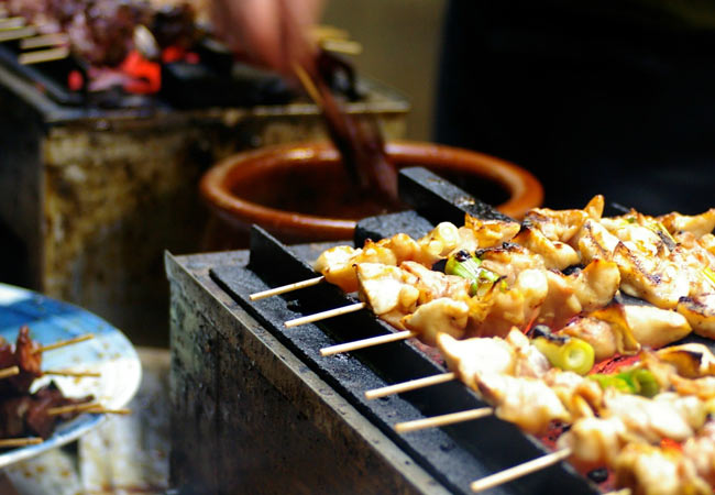 Yakatori chicken on a street stall grill in Tokyo with urbanadventures.com.