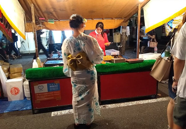 A Japanese woman in a Yukata buying food from a vendor during the Saki Matsuri celebrations.