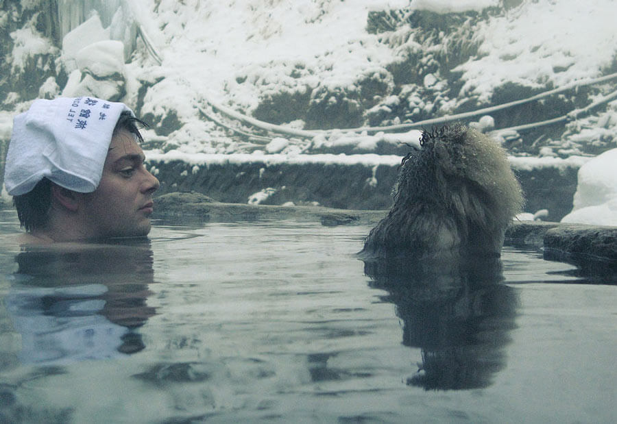 Man in onsen with snow monkey