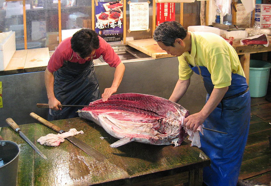 Fish being cut up at a fishmarket place.
