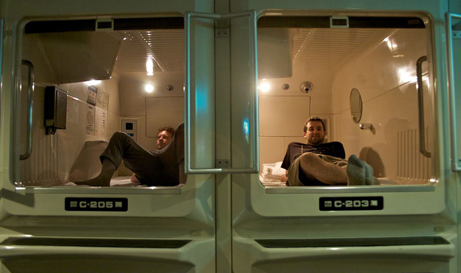 Two people getting ready to sleep at a capsule hotel at the Asahi Plaza.