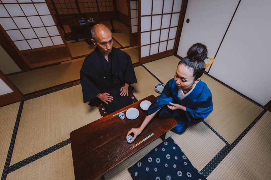 A Japanese couple sitting on tatami mats.